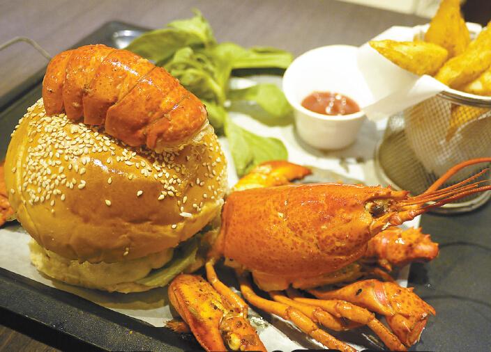 龍蝦牛肉漢堡每日限量100個,吸引不少人排隊購買。   【香港商報網訊】位於福田皇庭廣場的柏樂坊餐廳,今年1月份才剛開幕,但人氣已經相當不俗了,特別推出的招牌龍蝦漢堡最受食客歡迎,不少人特意過來排隊就是為了試試這個龍蝦漢堡,但其實除了龍蝦漢堡不能錯過,這裏的招牌甜品Reve不僅賣相好味道也一流,黑朱古力和咖啡的碰撞,讓人回味無窮,推薦指數直迫五粒星。   香港商報記者 羅嘉敏   要談柏樂坊不如先從Princess coco開始說起,Princess coco是一間在澳洲以製作甜品為主的餐廳,餐廳推